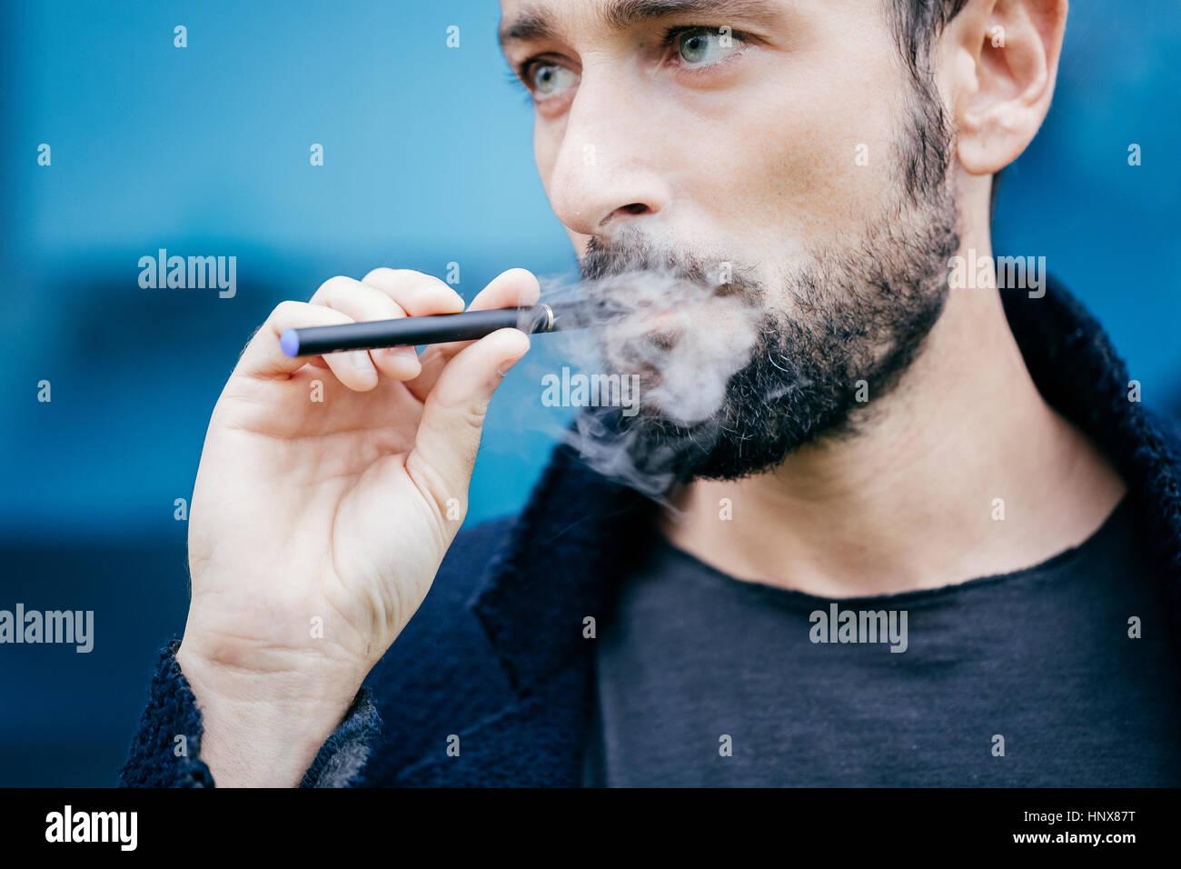 Portrait of man smoking an electronic cigarette - Stock Image