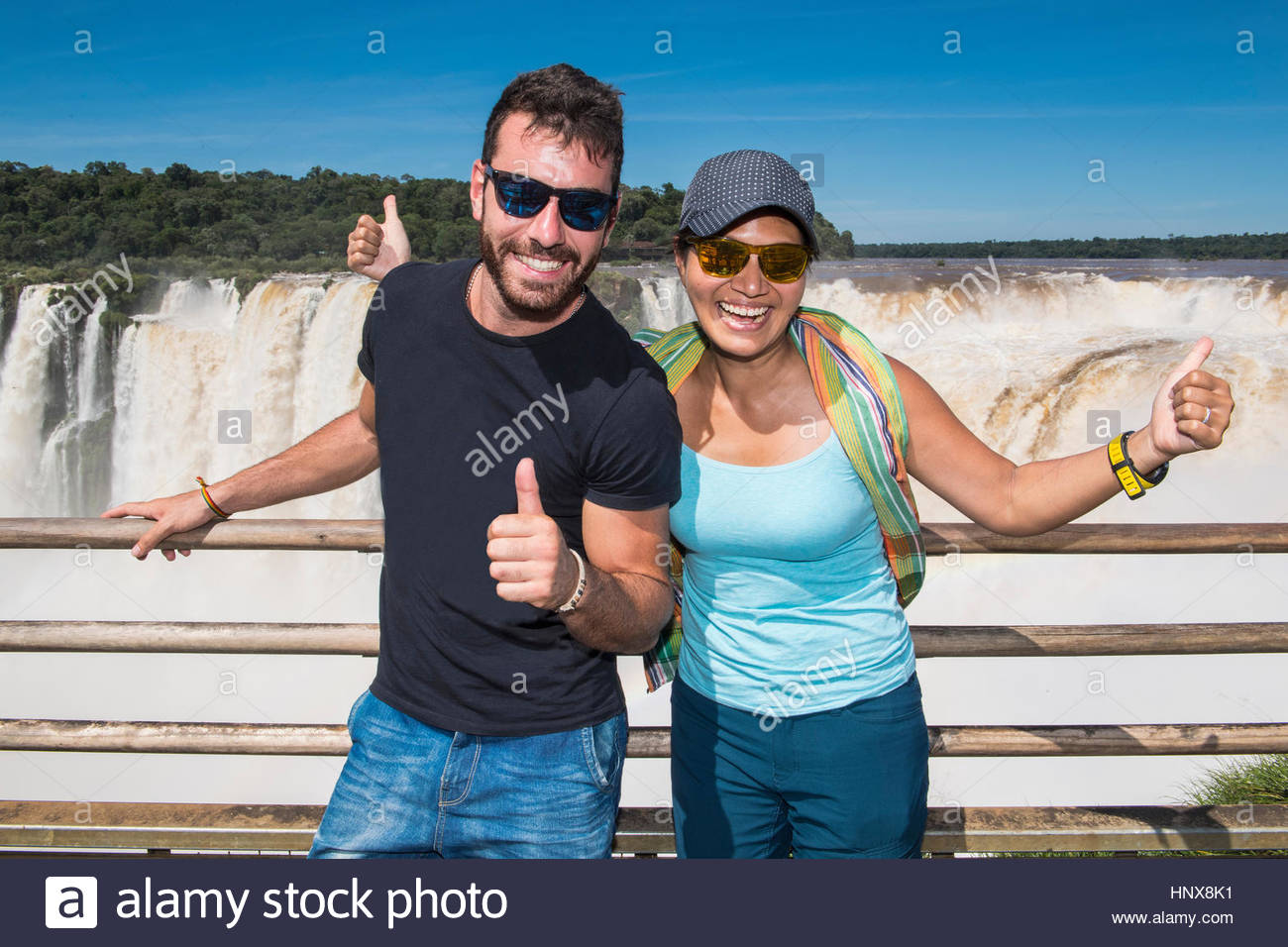 Couple posing at the devils throat in front of Iguazu falls, Misiones, Argentina - Stock Image