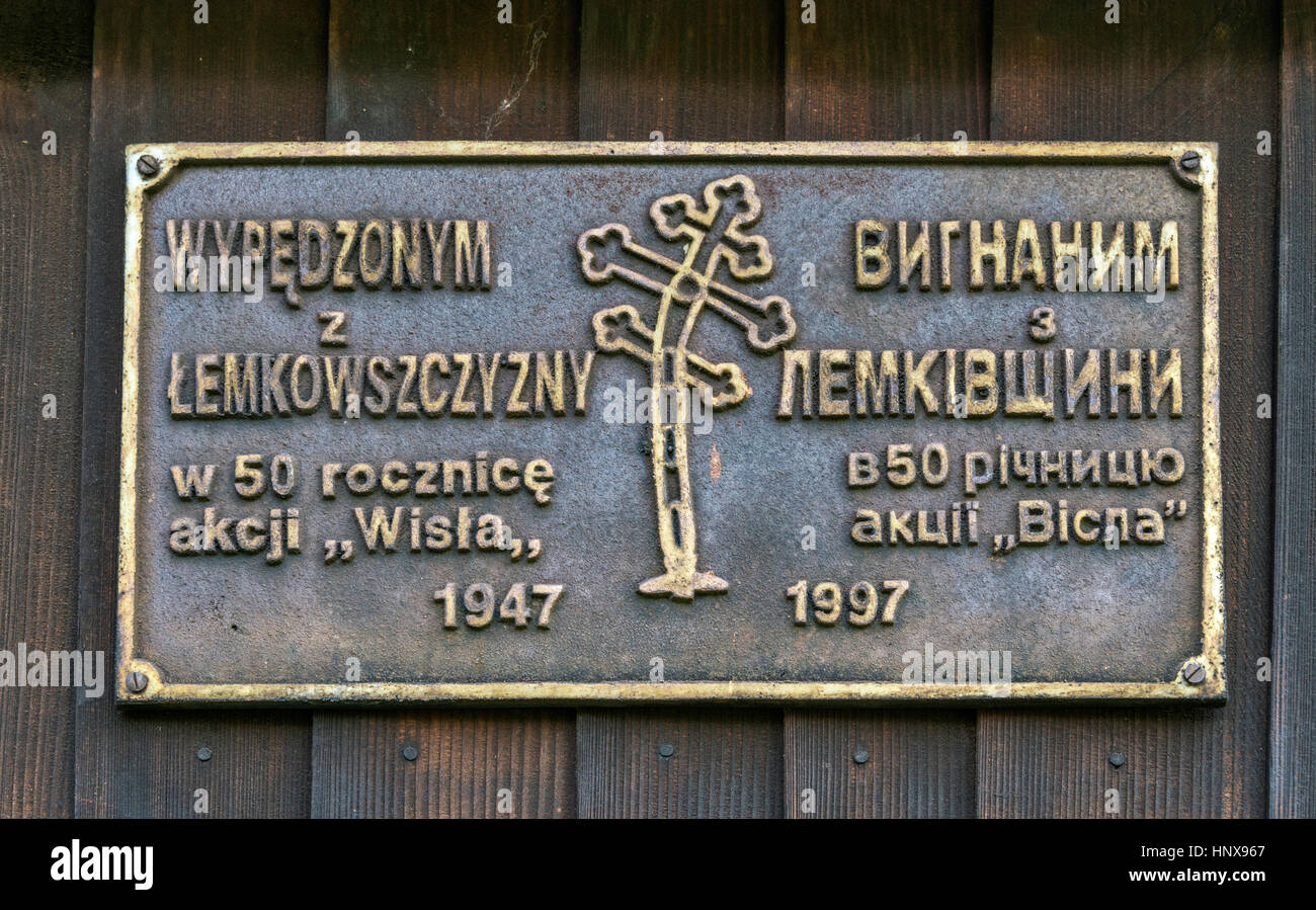 Bilingual Polish/Ukrainian sign commemorating forced resettlement of Ukrainian minority, at Saint Luke Church, Greek - Stock Image