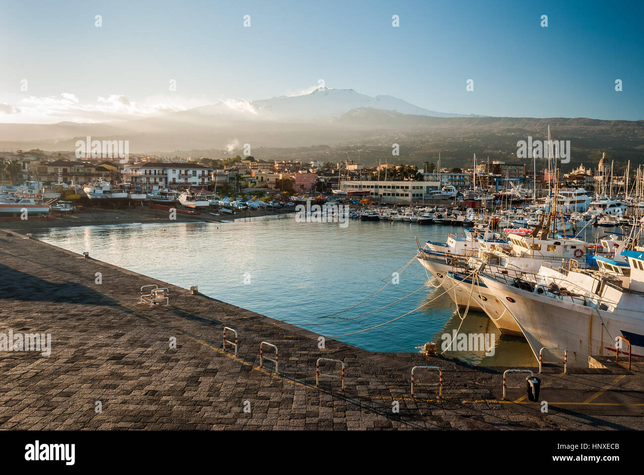 The harbor of Riposto during the sunset; snowy volcano Etna in the background - Stock Image