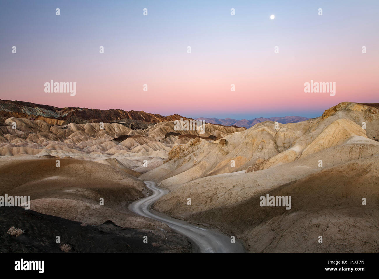 Moon, badlands and road, Twenty Mule Team Canyon, Death Valley National Park, California USA - Stock Image