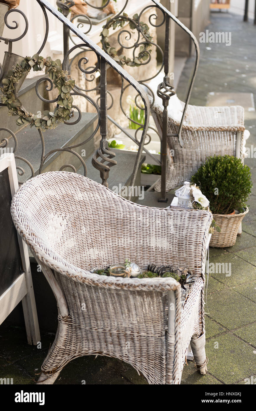 HATTINGEN, GERMANY   FEBRUARY 15, 2017: White Painted Woven Willow Chairs  And Green Plants Decorate A Retail Storefront