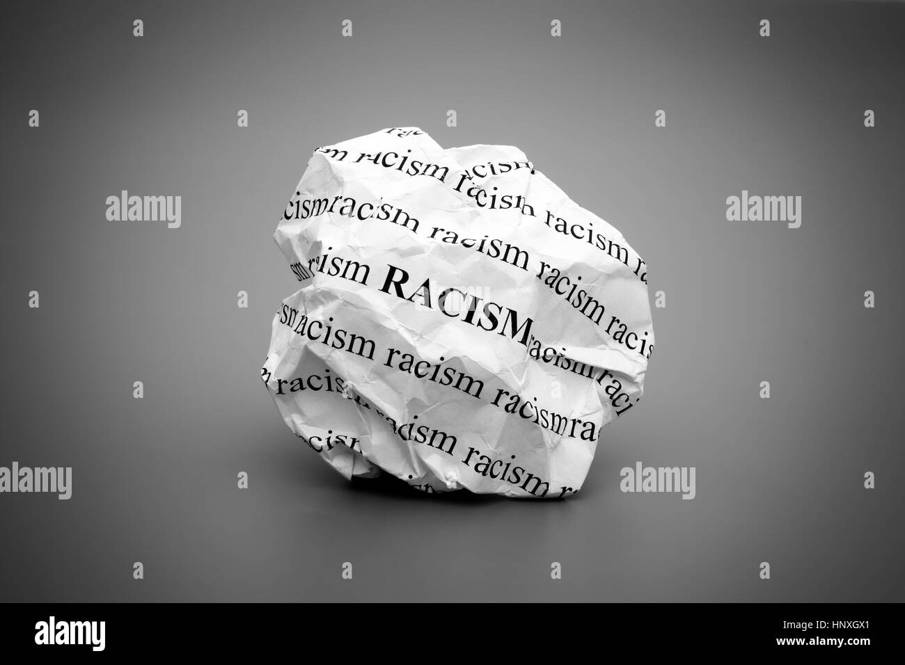 Crumpled paper ball with words Racism on gray background. Black and white. - Stock Image