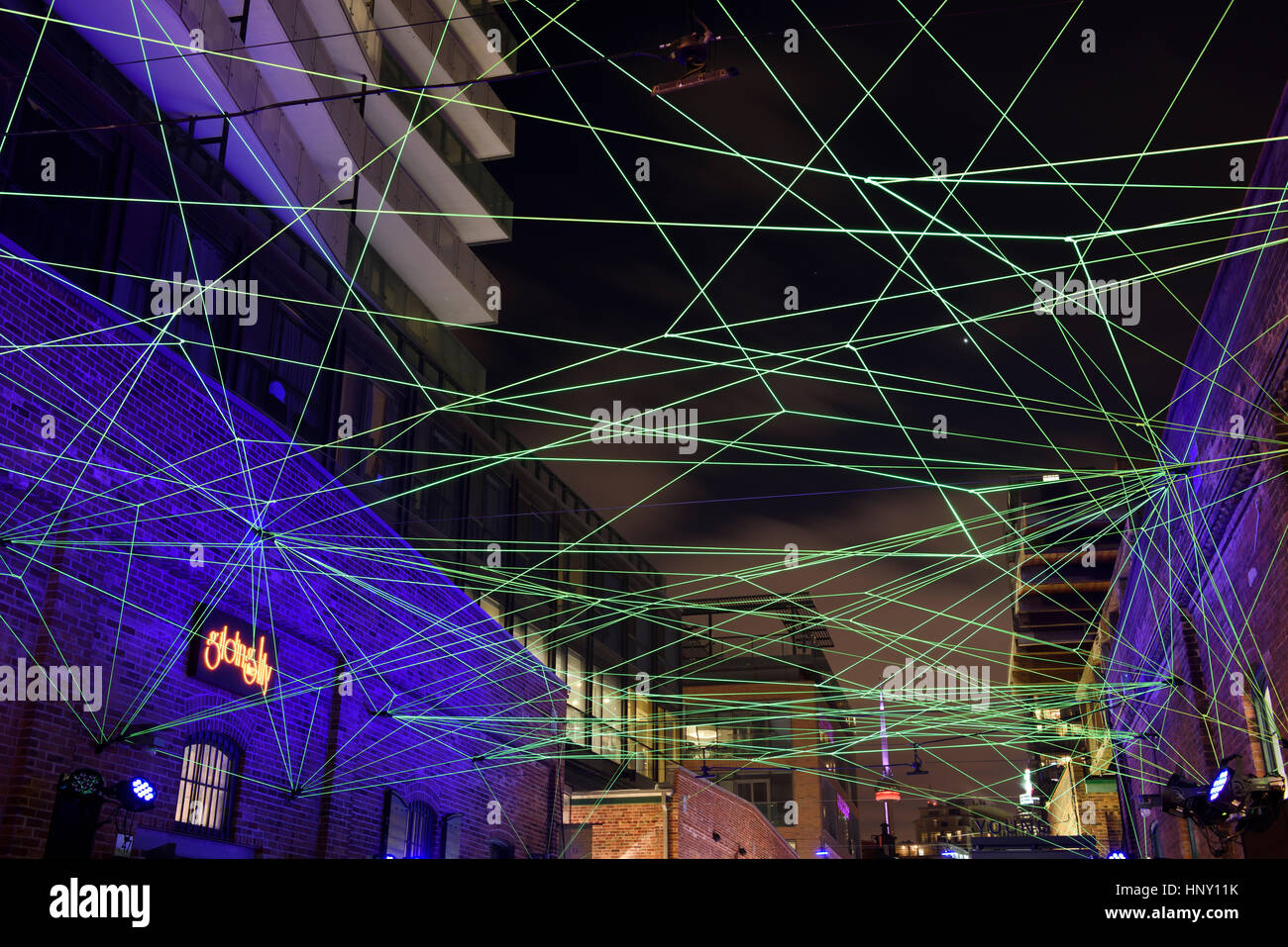 Green fiber optic cables art installation at Toronto Light Festival at Distillery District with CN Tower at night - Stock Image