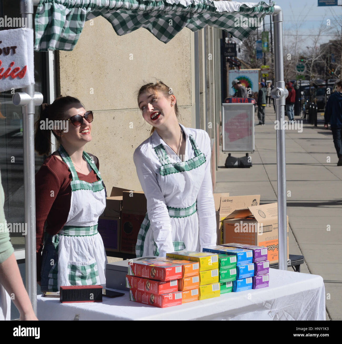 Purveyors of Girl Scout Cookies talk while working at a stand in downtown Boulder, CO - Stock Image