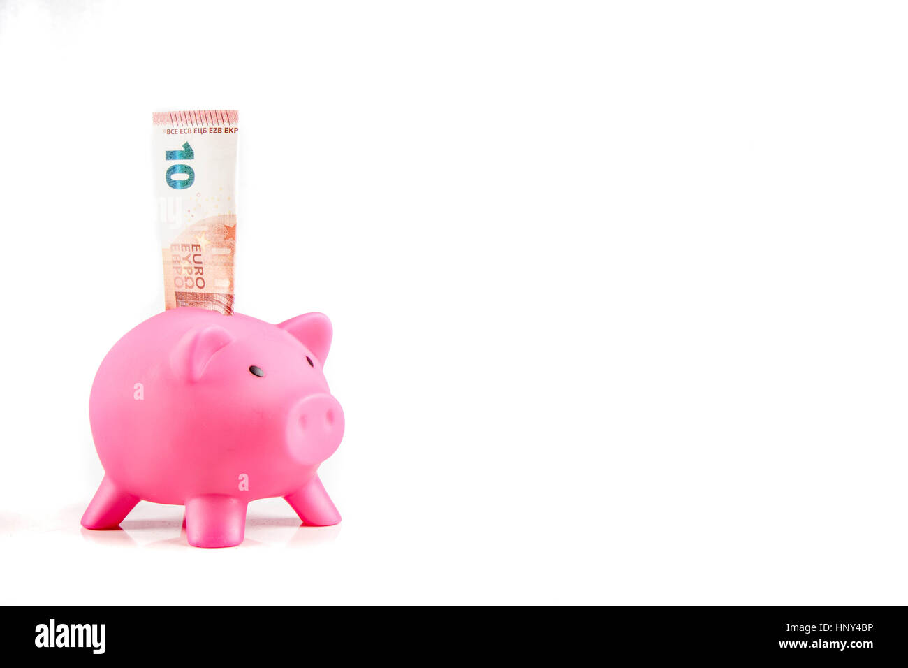 Piggy bank with ten Euro banknote landscape orientation with copyspace - Stock Image