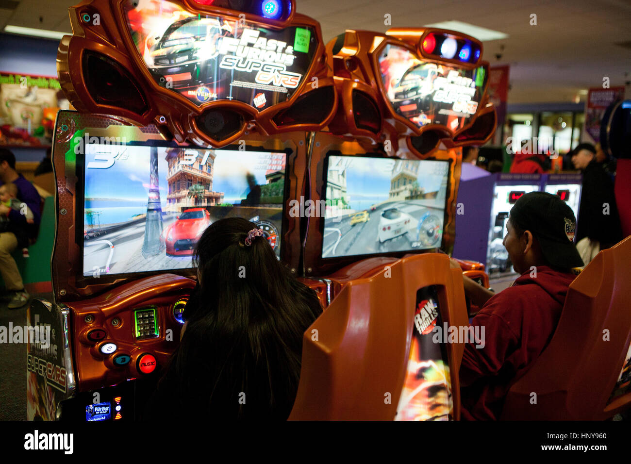 People playing auto racing video game at video arcade - USA - Stock Image