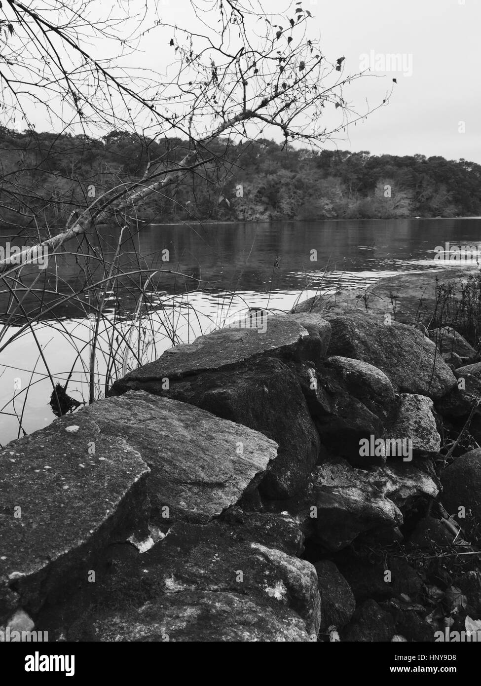 Black and white photo of a rock wall near a pond - Stock Image