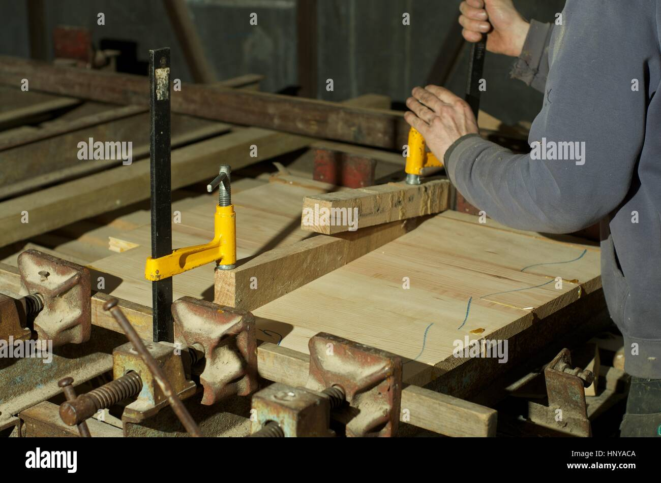 Carpenter placing wood in a press for gluing - Stock Image