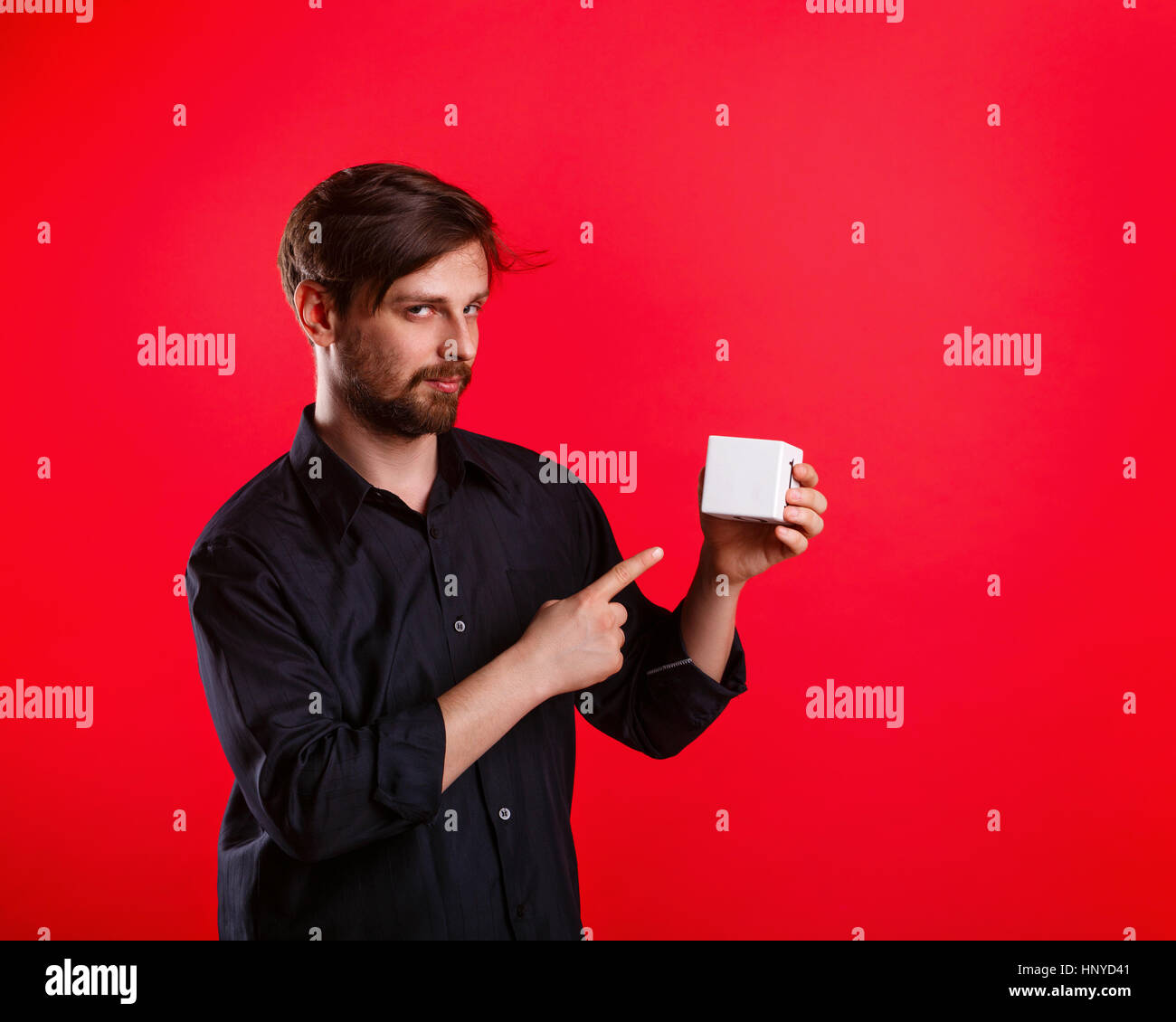 Man holding an empty cube. Advertising Space. Attractive man shows space for copy. Forefinger. Tricky glance - Stock Image
