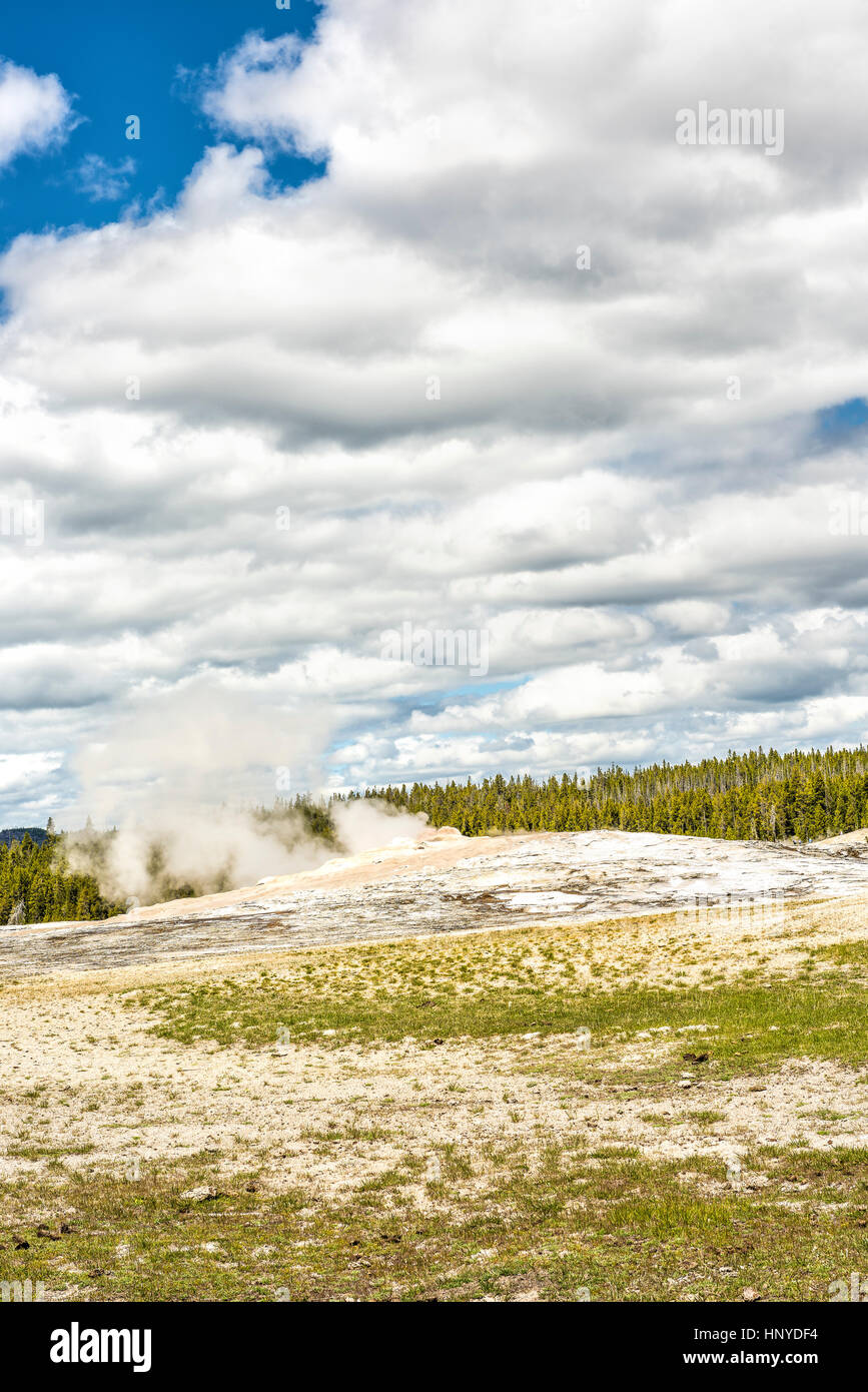 Old Faithful Geyser waiting to erupt in Yellowstone National Park with steam and clouds - Stock Image