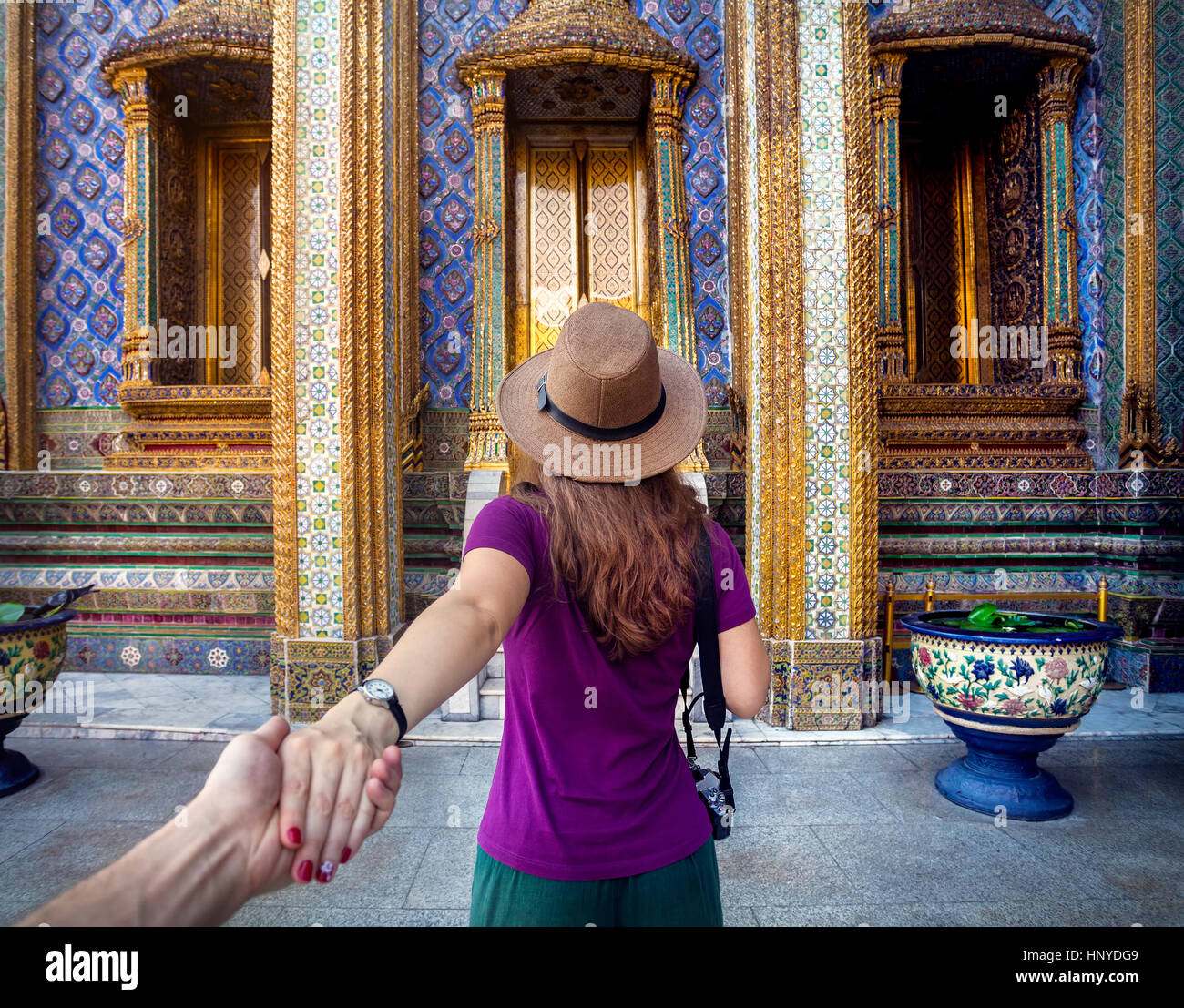 Woman in hat and purple t-shirt leading man by hand to the Wat Phra Kaew famous temple in Bangkok, Thailand - Stock Image