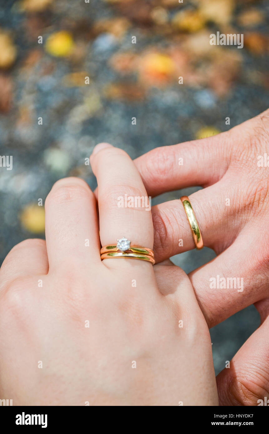 Husband and wife hands with marriage wedding rings on fingers Stock