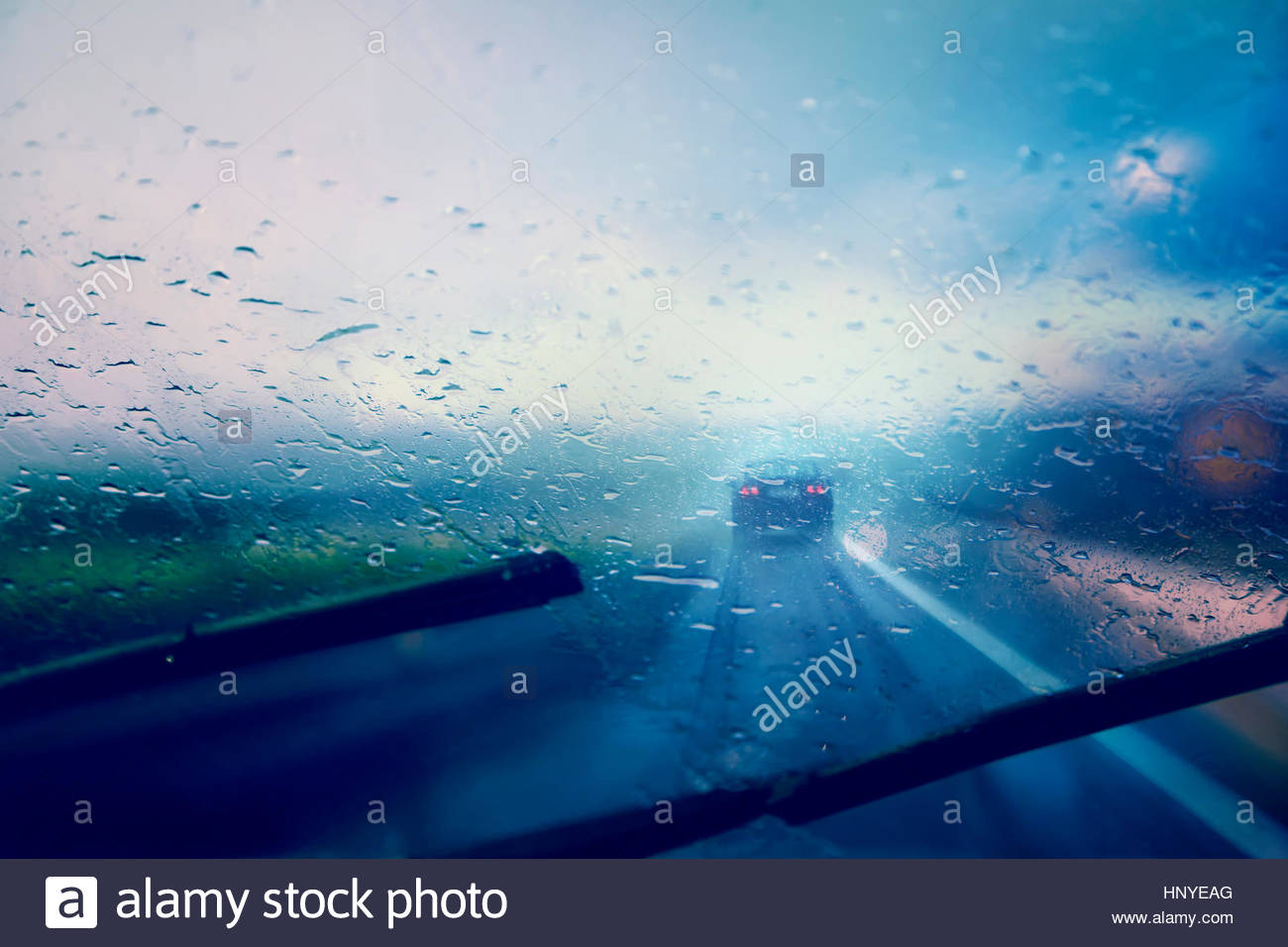 Dangerous vehicle driving in the heavy rainy and slippery road. Raindrops on windshield of moving car on highway. - Stock Image