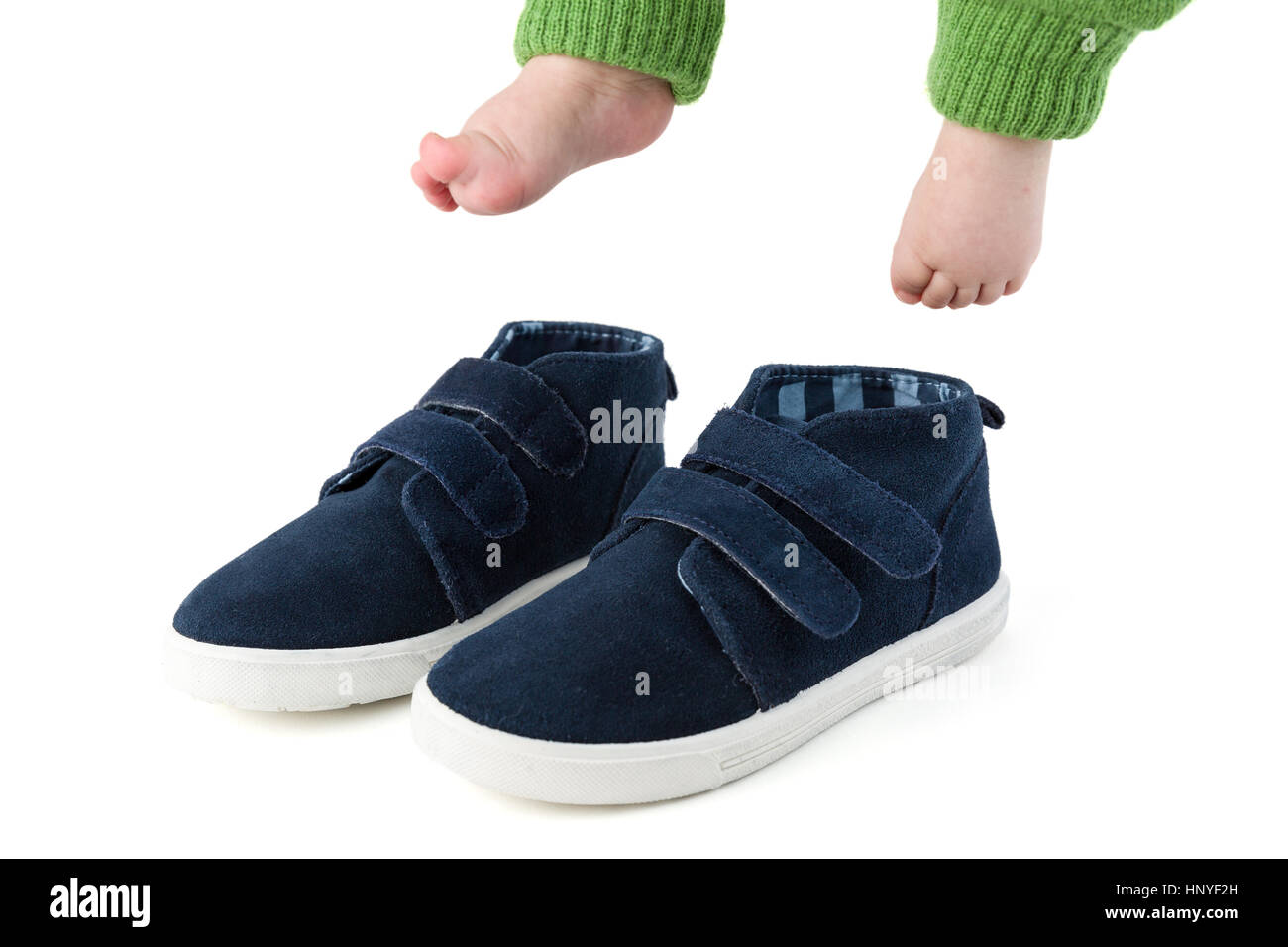 Baby feet with too big blue child shoes isolated on white studio shot - Stock Image