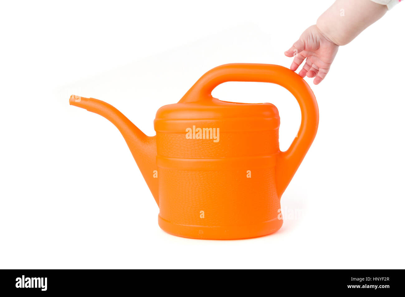 Baby trying to grab orange watering can on white background studio shot - Stock Image
