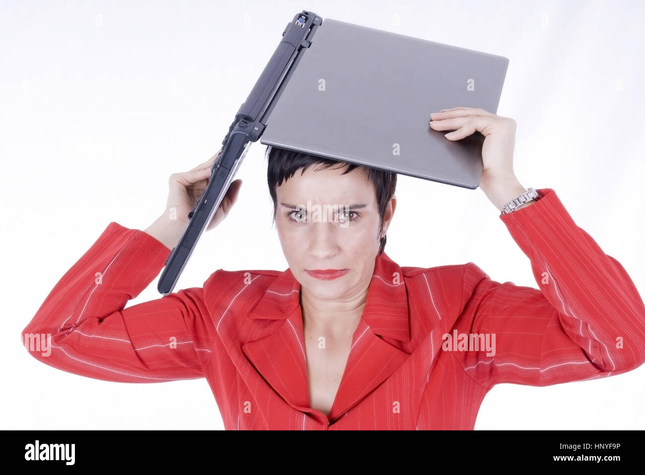 Model release , Veraergerte Businessfrau mit Laptop ueber dem Kopf - business woman with laptop Stock Photo