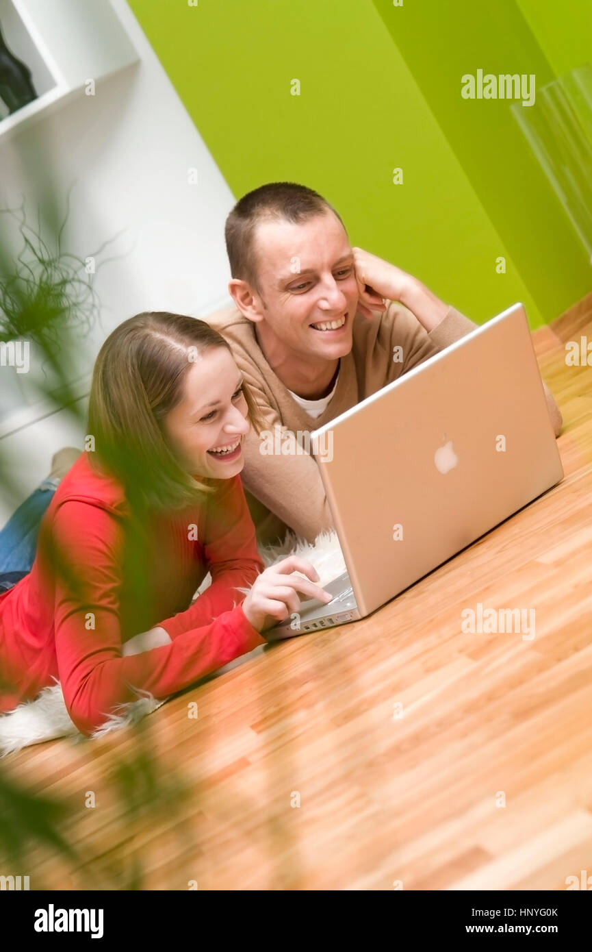 Model release , Paar sitzt gemeinsam mit Laptop am Wohnzimmerboden - couple in living room using laptop - Stock Image