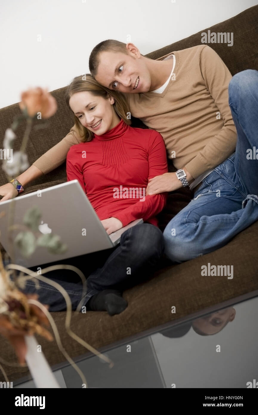 Model release , Junges Paar sitzt mit Laptop auf der Couch - couple using laptop on couch Stock Photo