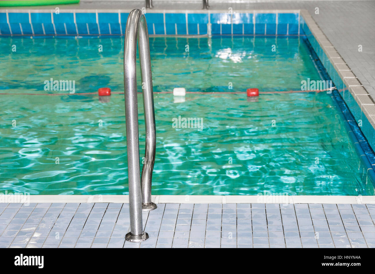 A rope marks the border between the lanes in an indoor swimming pool. - Stock Image