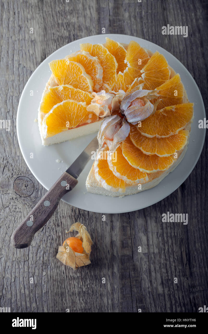 Cheesecake decorated with oranges and physalis. Stock Photo