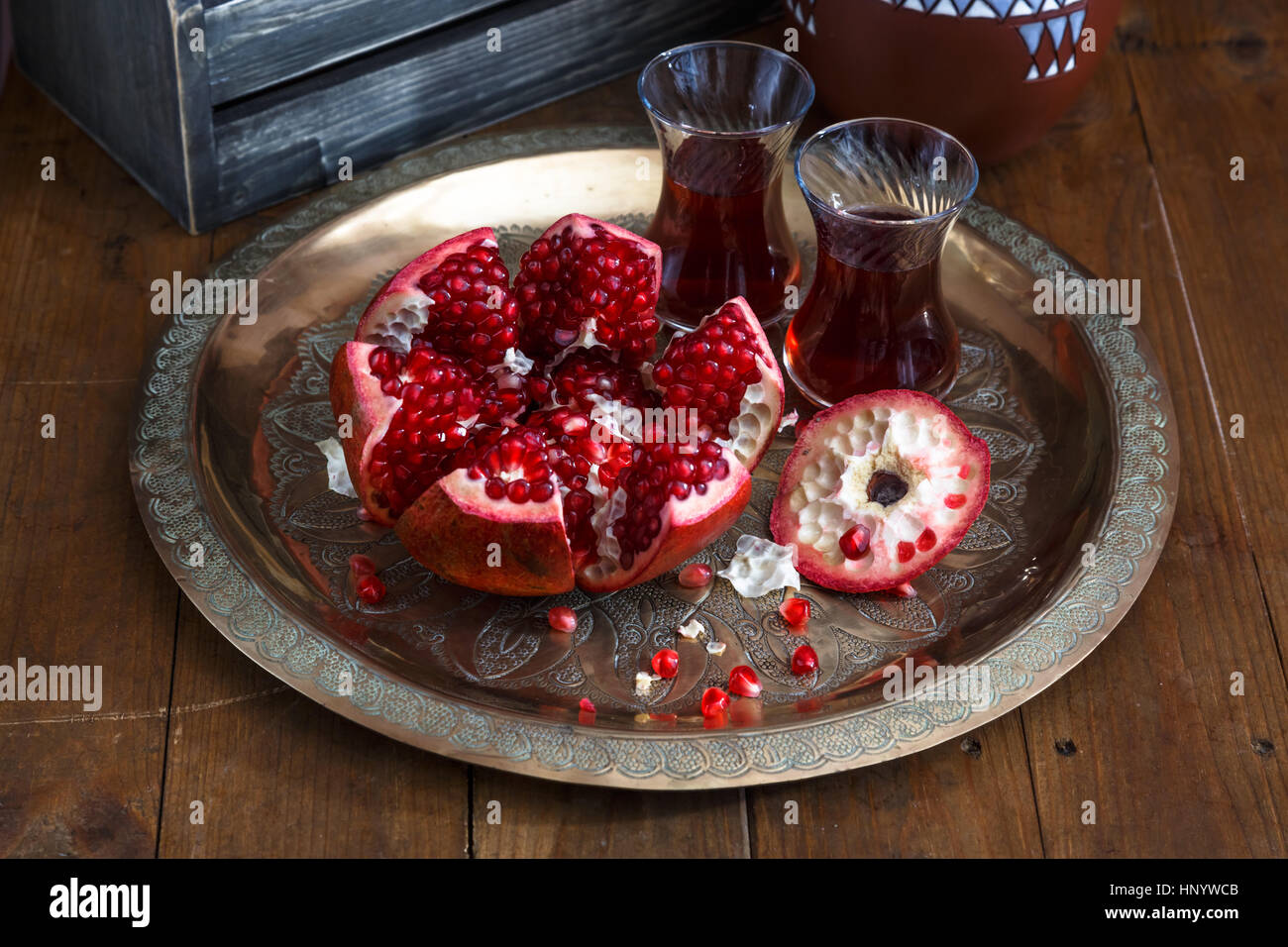 ripe pomegranate on copper plate on a dark background, close view Stock Photo