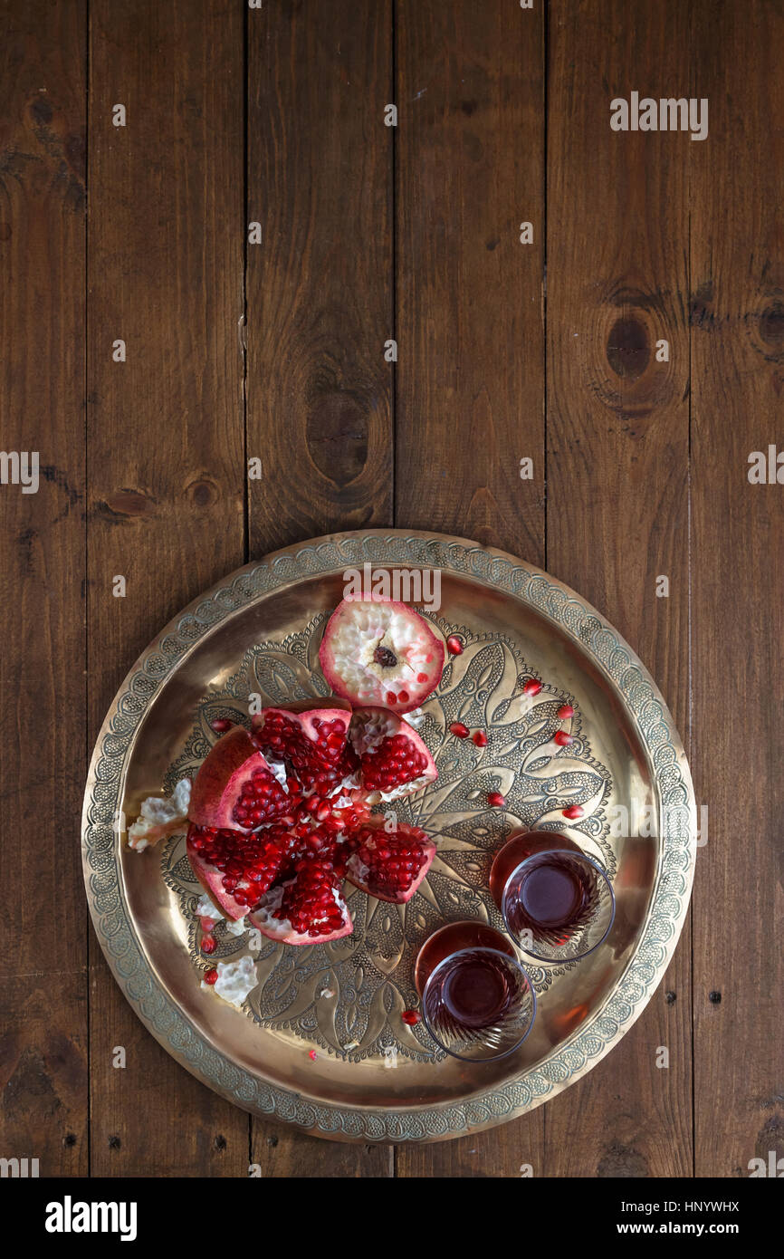 Ripe pomegranates with juice on copper plate on wooden background, top view - Stock Image