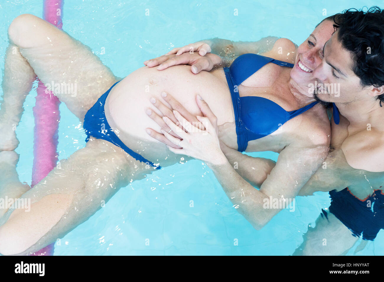 Pregnant woman exercising in swimming pool with help of partner and flotation devices Stock Photo