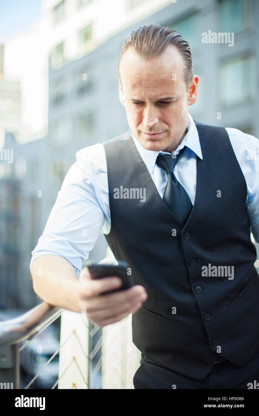 Businessman text messaging with cell phone - Stock Image