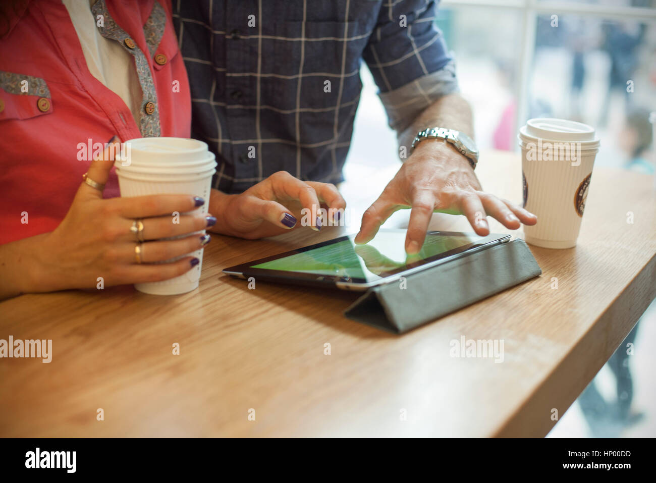 Couple using digital tablet in coffee shop, cropped - Stock Image