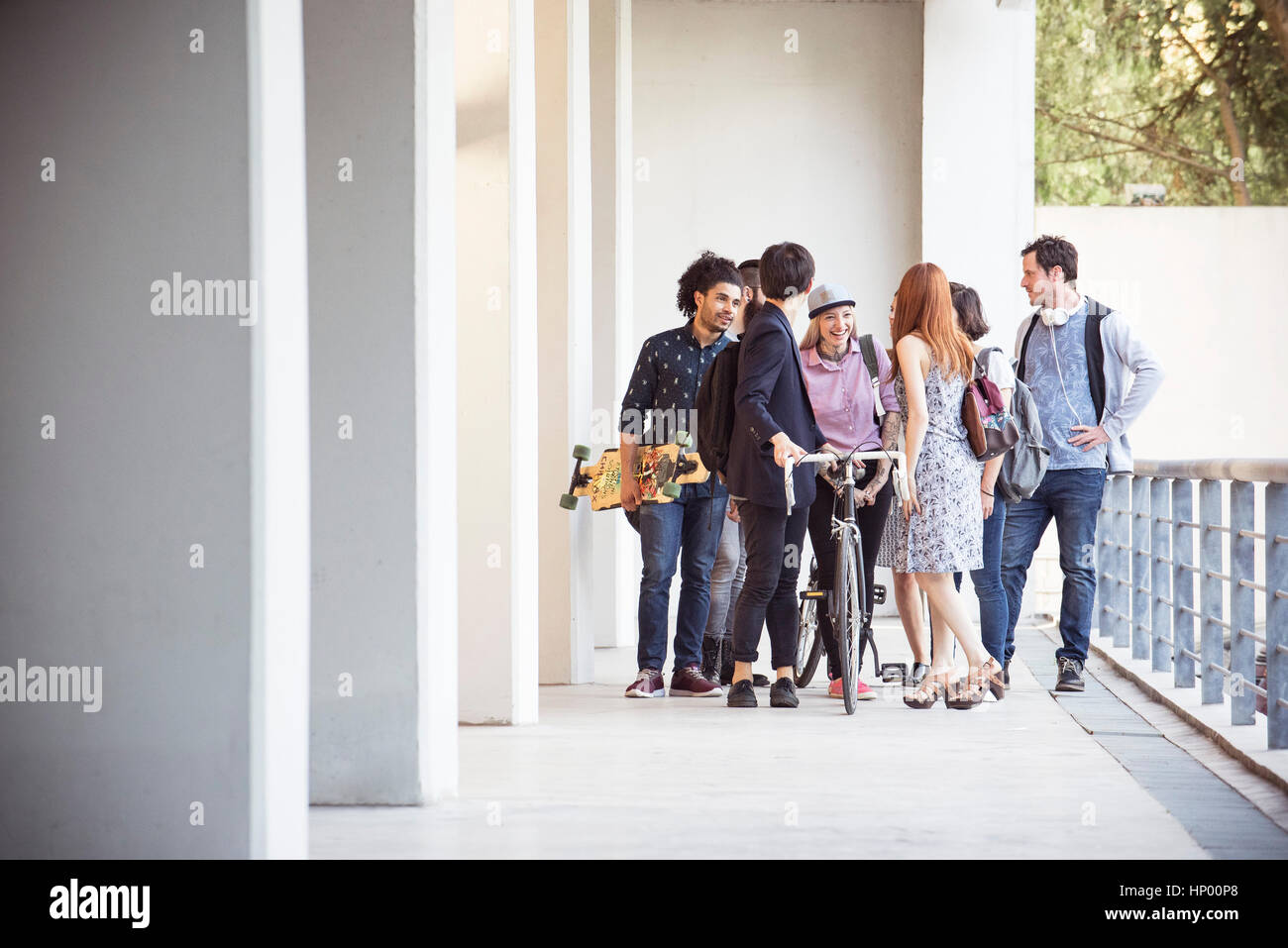 Group of college students chatting together after class - Stock Image