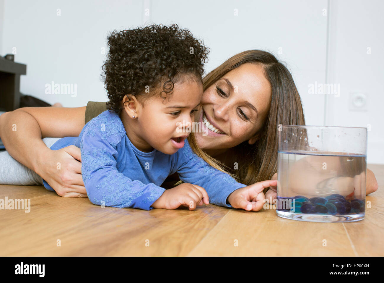 Mother and toddler daughter looking at pet goldfish Stock Photo
