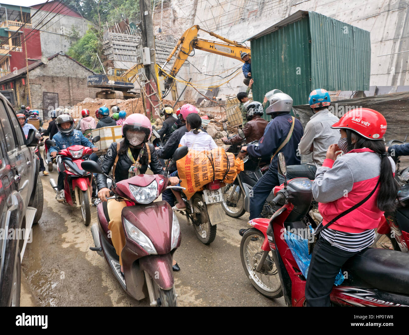 People riding scooters & motorcycles, wearing helmets & protective gear, city street, parked automobile, - Stock Image
