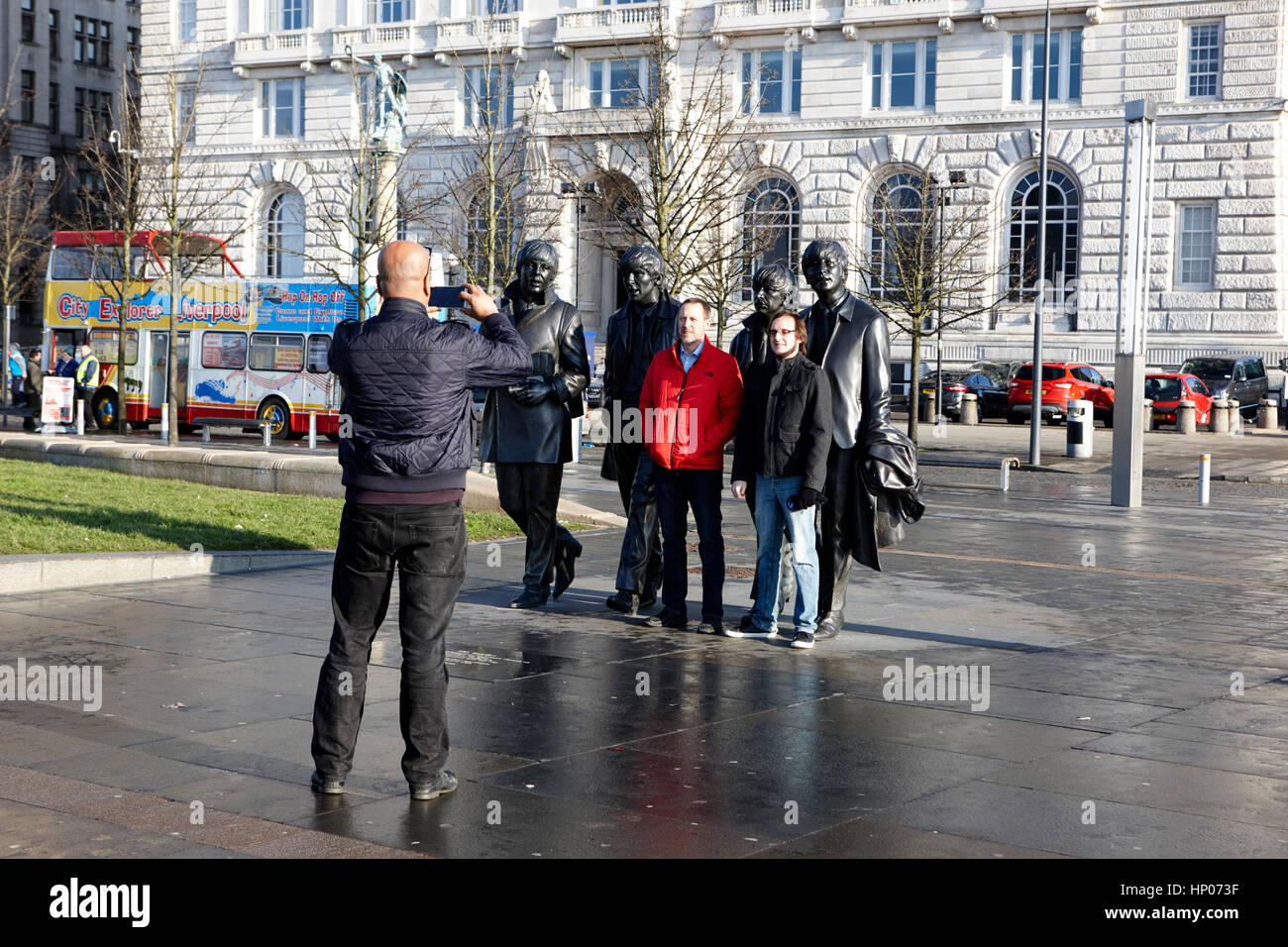 tourists taking photos with the beatles statue in front of pier head landmark buildings liverpool uk - Stock Image