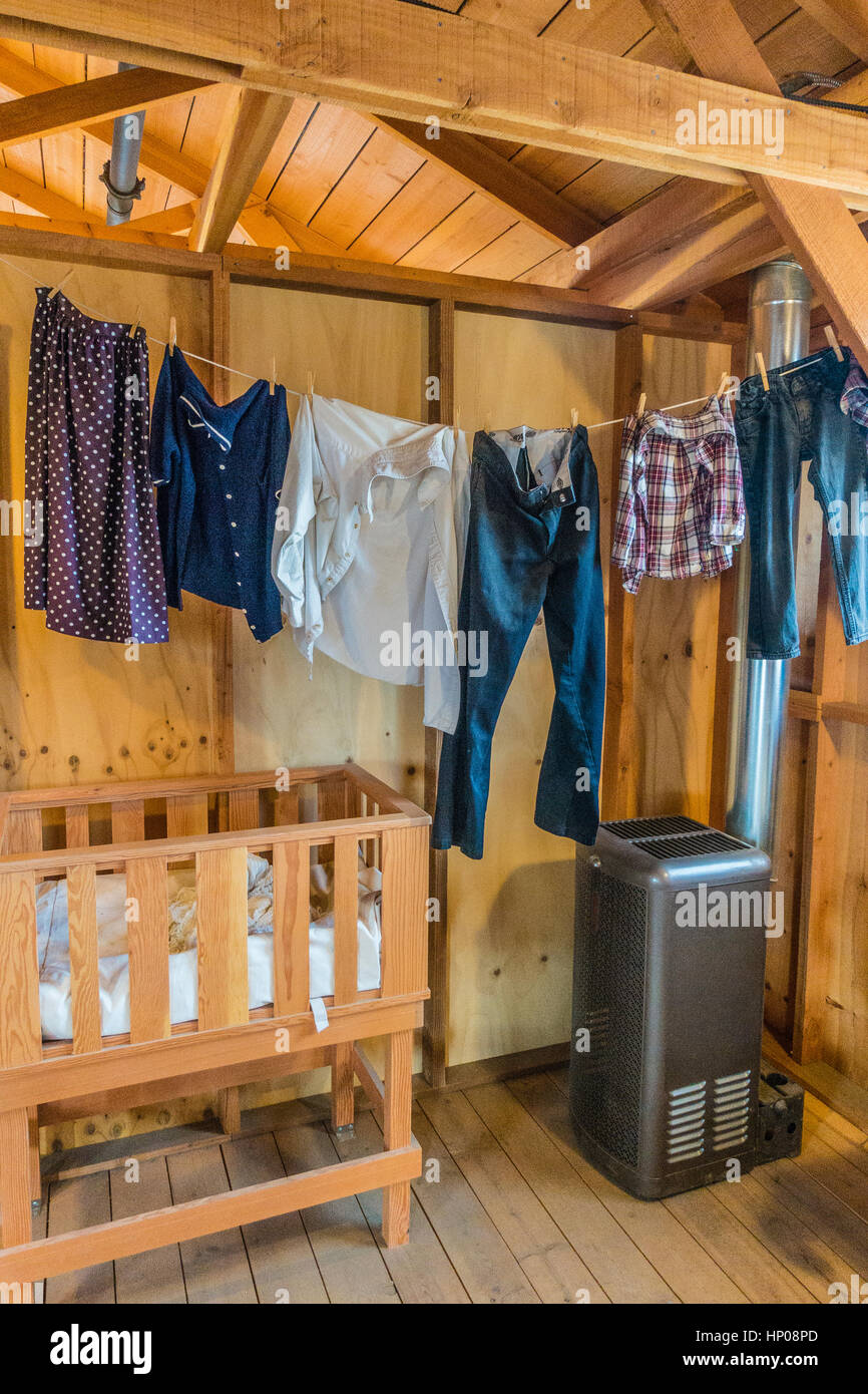 Manzanar housing inside with a clothesline with fresh laundry hanging from it, a small heater and a wooden crib. - Stock Image