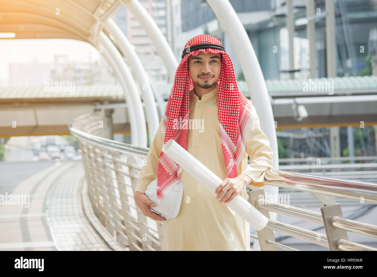 Happy handsome arab business standing outdoor with  city background. - Stock Image