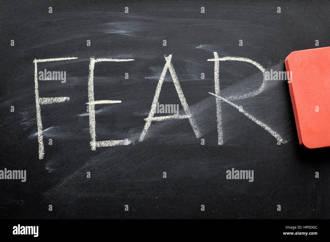erasing fear, hand written word on blackboard being erased concept - Stock Image