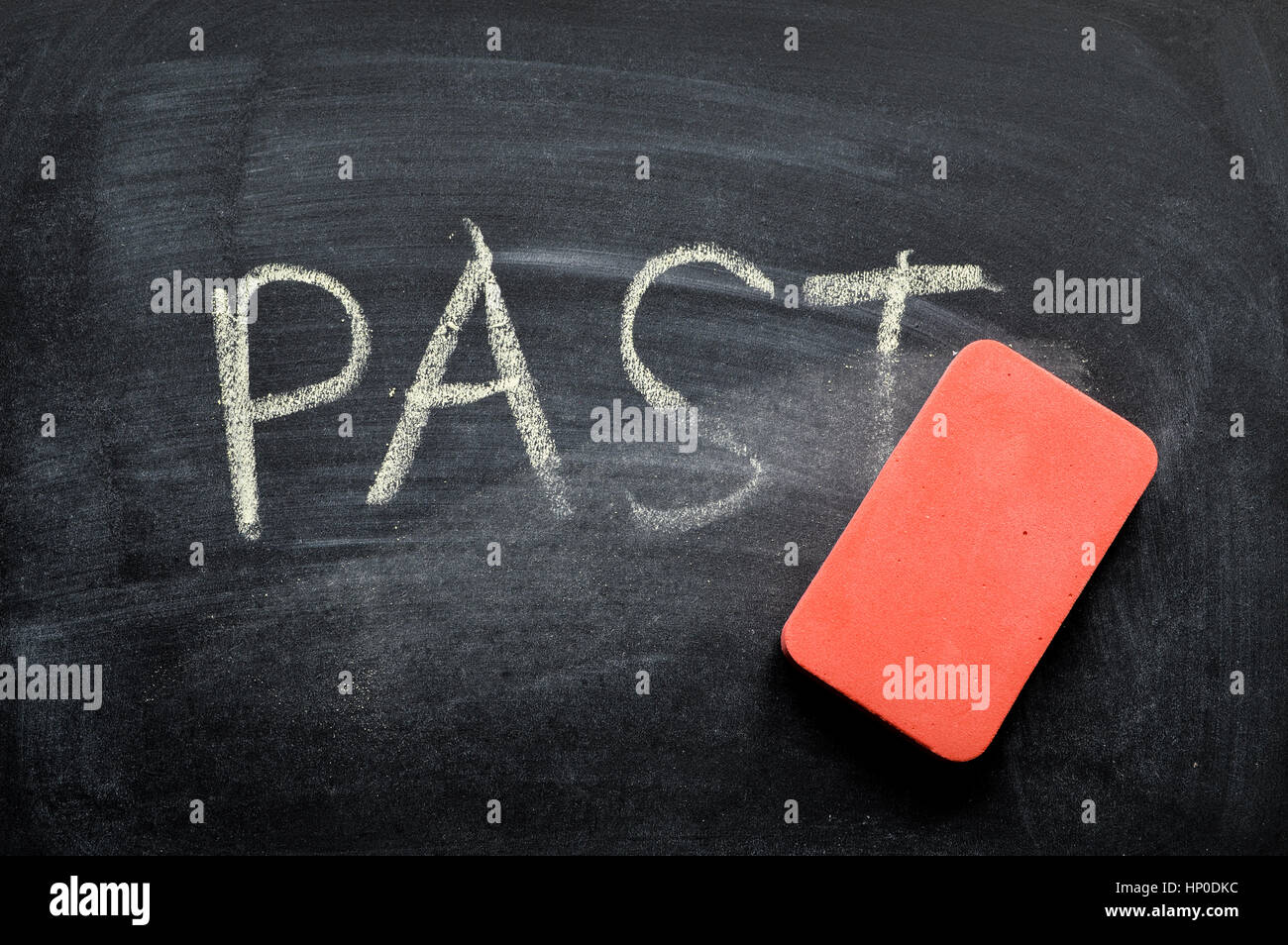 erasing past, hand written word on blackboard being erased concept - Stock Image