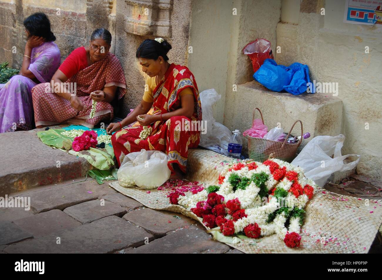 Local ladies making flower garlands for temple-goers at the foot of the Rock Temple in Thanjavur, Tamil Nadu, Southern - Stock Image