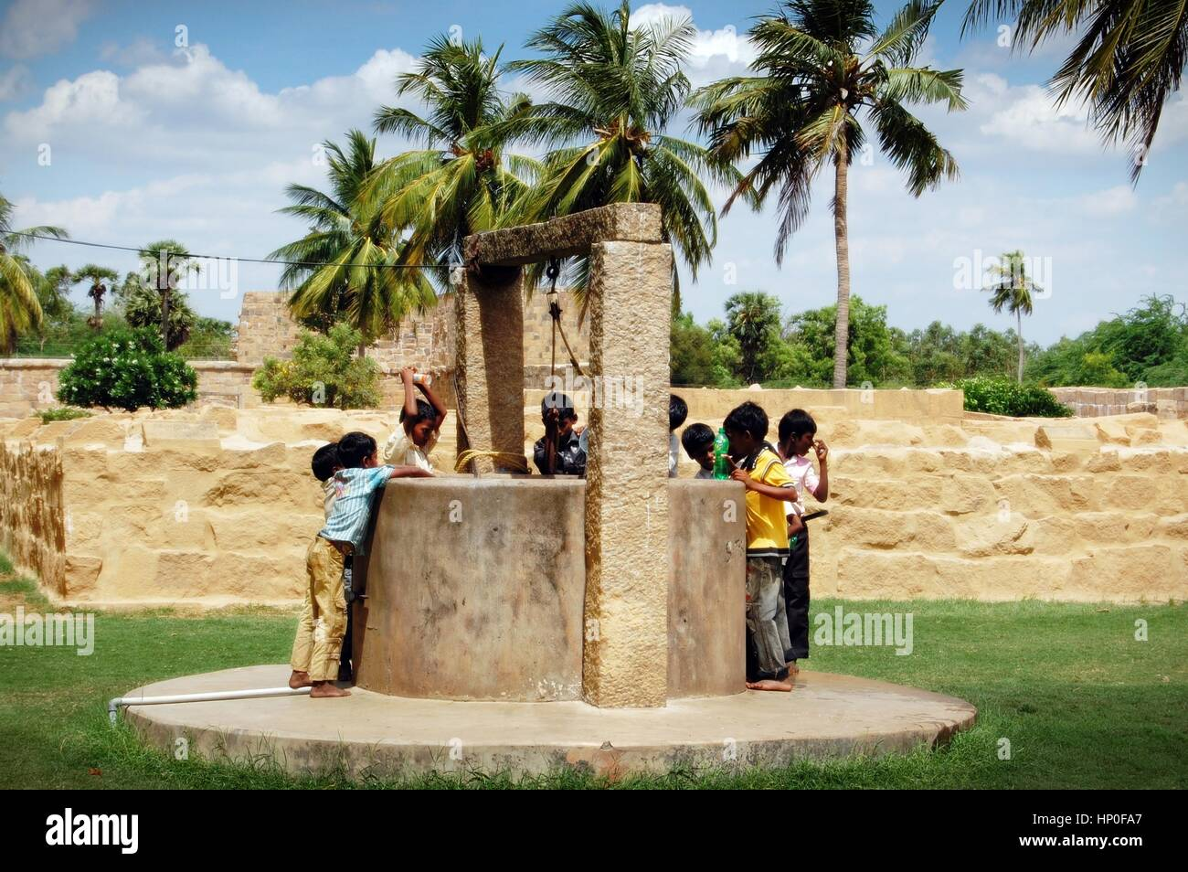 Indian boys gather at the well to draw water on a blazing hot day in tamil nadu south india