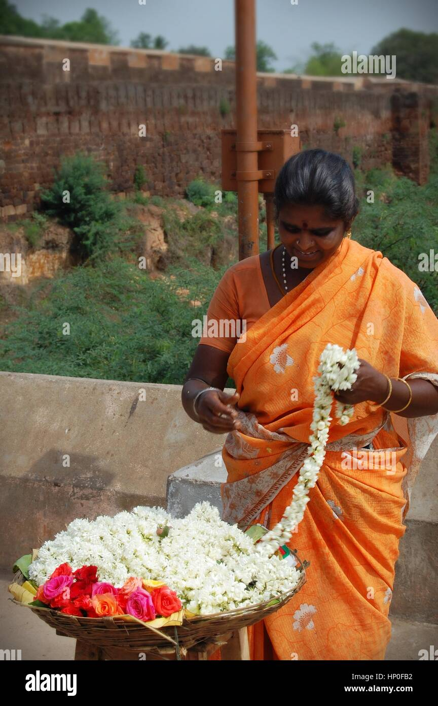 Indian woman in orange sari threading jasmine flowers into a garland outside a temple, Tamil Nadu, South India - Stock Image
