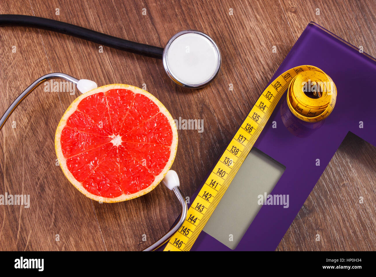 Digital electronic bathroom scale for weight of human body, tape measure and medical stethoscope with fresh grapefruit, - Stock Image