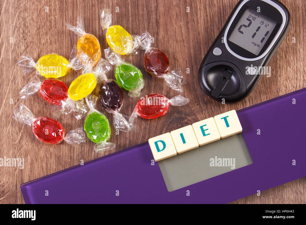 Electronic bathroom scale and glucose meter with high result of measurement sugar level and heap of colorful candies, - Stock Image