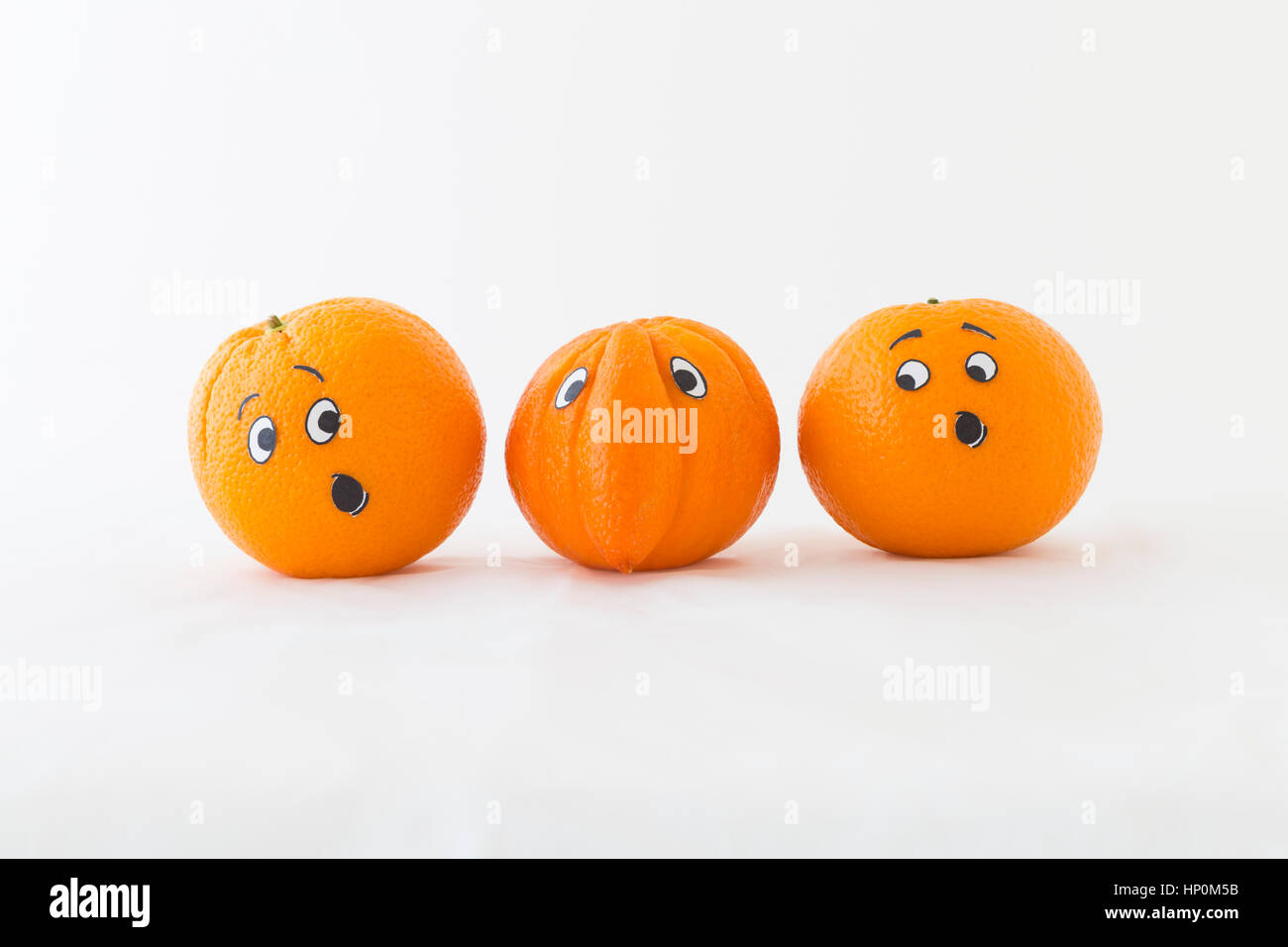 Fresh oranges with funny faces in front of white background. One orange has a huge nose - Stock Image