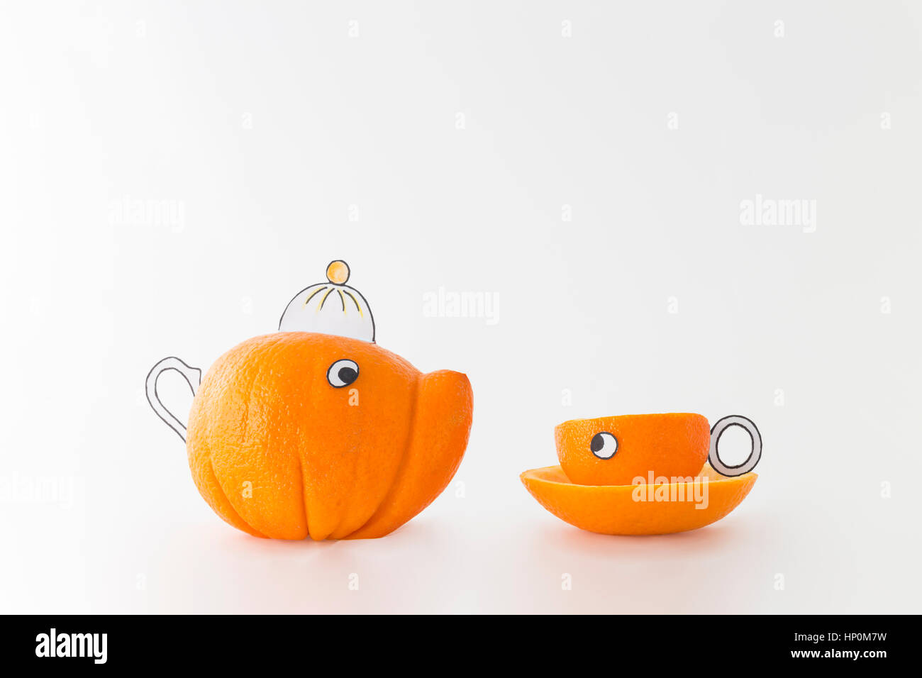 Funny tea cup and pot made from fresh oranges in front of white background - Stock Image