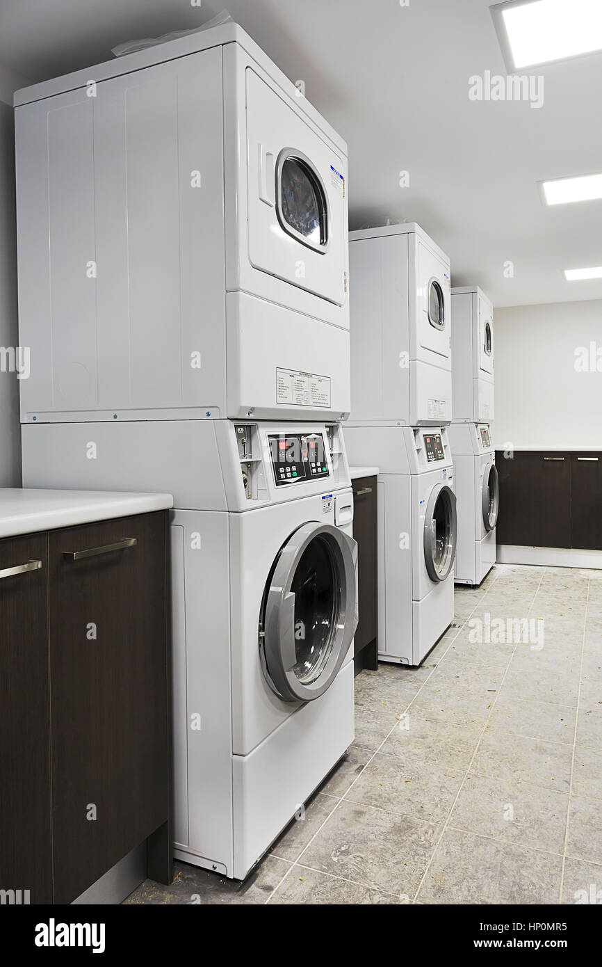 Automatic washing machine service for customers in commercial laundromat with dryers and washers ready to work. - Stock Image