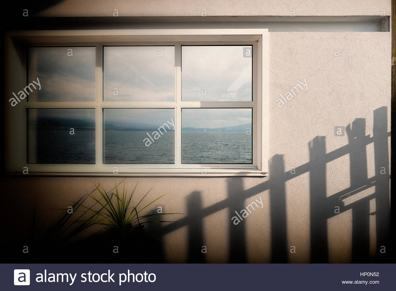 Window sea view fence shadow white wall - Stock Image