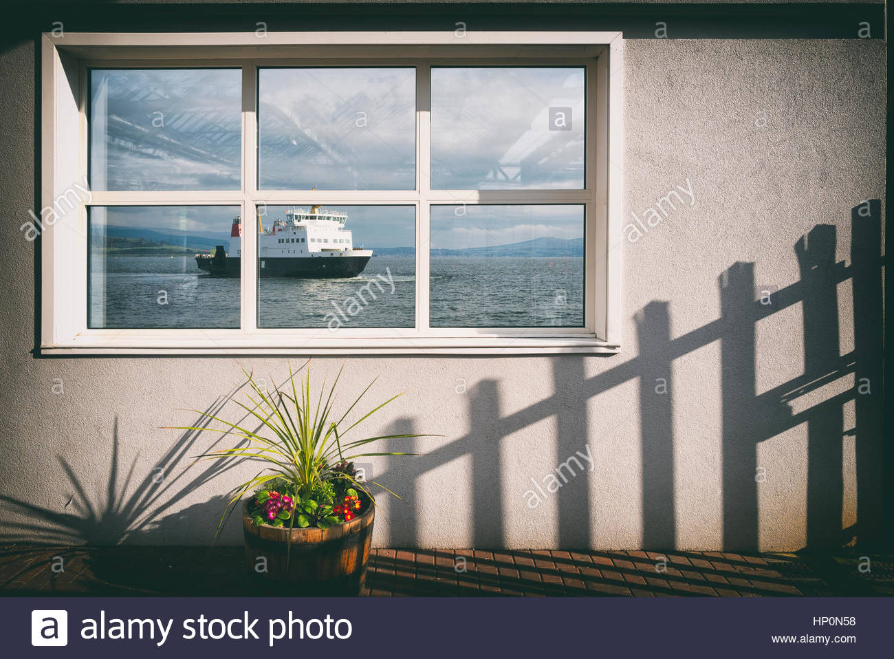 Window sea view fence shadow white wall ferry boat - Stock Image