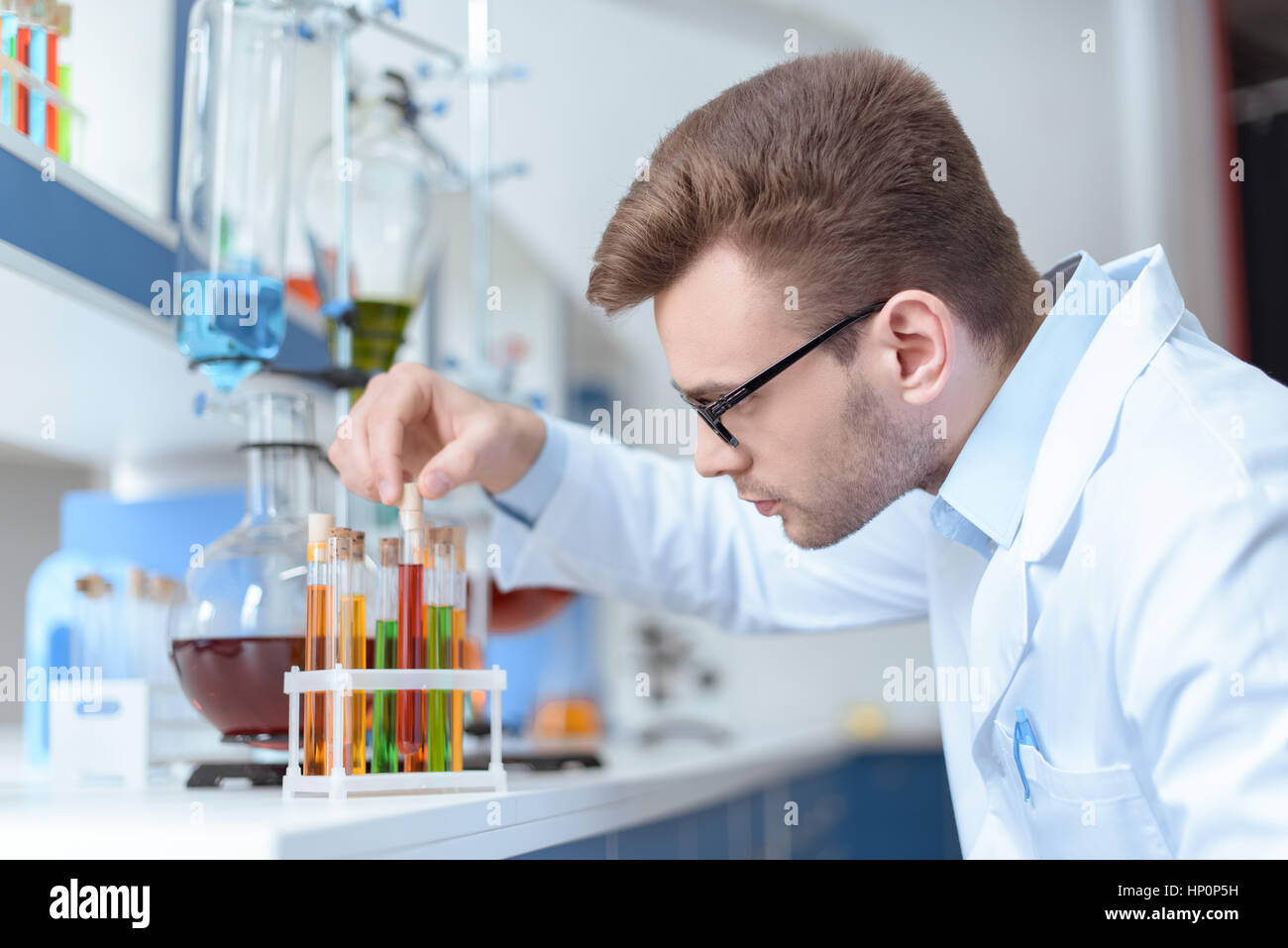 young man scientist holding test tube with reagent in lab - Stock Image
