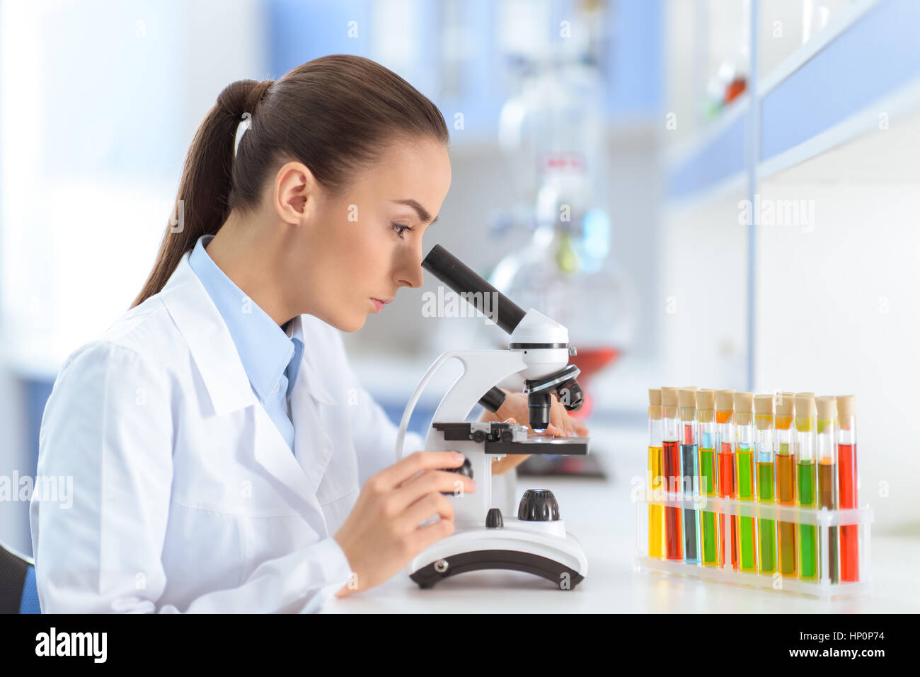 woman scientist working with microscope in laboratory - Stock Image